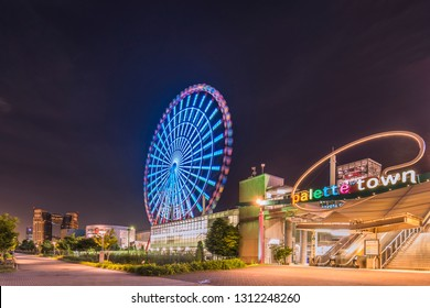 TOKYO, JAPAN - August 24 2018: Odaiba illuminated Palette Town Ferris wheel named Daikanransha visible from the central urban area of Tokyo in the summer night sky. Passengers can see the Tokyo Tower,