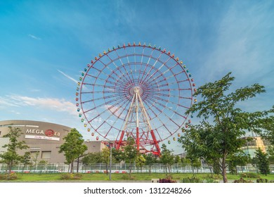 TOKYO, JAPAN - August 24 2018: Odaiba colorful tall Palette Town Ferris wheel named Daikanransha visible from the central urban area of Tokyo in the summer blue sky. Passengers can see the Tokyo Tower