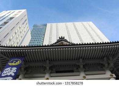 TOKYO, JAPAN - August 24, 2018: View of part Ginza's Kabuki-za kabuki theater's roof with a banner with its phoenix motif on it and the Kengo Kuma-designed Kabuki-za Tower above it.