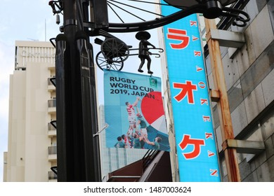 TOKYO, JAPAN - August 24, 2019: A banner promoting the 2019 Rugby World Cup on lamppost in Tokyo's Akasaka area. The lamppost features a rickshaw & its driver. Behind it is a sign on a karaoke parlor.