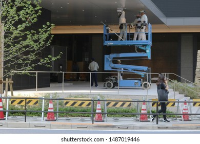TOKYO, JAPAN - August 24, 2019: Workers on a crane work on the lighting at an entrance to the Tokyo's new Hotel Okura Prestige Tower before its opening. Some motion blur.
