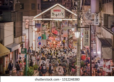 TOKYO, JAPAN - August 25 2018: Japanese bear Shinto shrine mikoshi on their shoulders during the Obon festival in the retro old-fashionned shopping street Yanaka Ginza famous as a spectacular spot for
