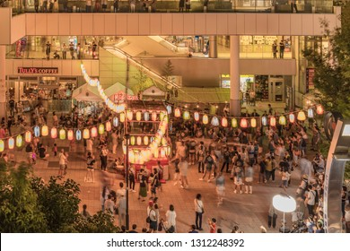 TOKYO, JAPAN - August 25 2018: View of the square in front of the Nippori train station decorated for the Obon festival with illuminated paper lanterns  in the summer night with a yagura tower and pap