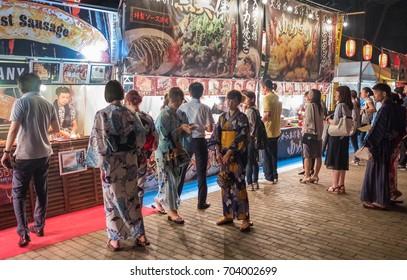TOKYO, JAPAN - AUGUST 25TH, 2017. Customers at the street food vendors at Hibiya park during Bon Odori festival celebration.