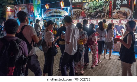 TOKYO, JAPAN - AUGUST 25TH, 2017. Customers at the street food vendors at Hibiya park during Bon Odori festival celebration.