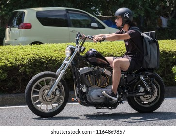 TOKYO, JAPAN - AUGUST 25TH, 2018. Man riding a classic motorcycle in the street of Yoyogi Park