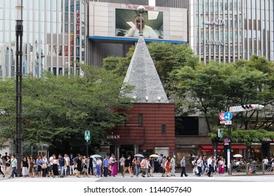 TOKYO, JAPAN - August 26, 2017: Pedestrians start crossing the crossing in front of the landmark Kazumasa Yamashita-designed Sukiyabashi police box overlooked by a giant TV screen the Lumine building.