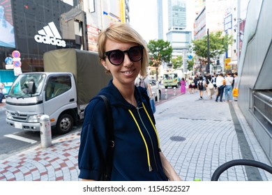 TOKYO JAPAN - AUGUST 26, 2018 : Happy touris walks the streets of Tokyo. Young girl with short hair in sunglasses.