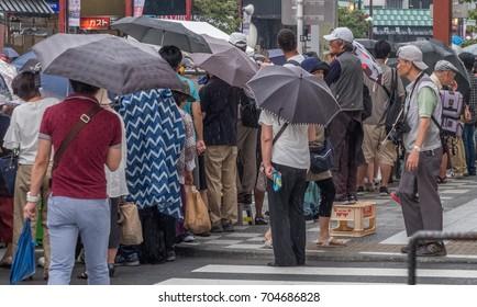 TOKYO, JAPAN - AUGUST 26TH, 2017. Spectators waiting by the roadside at the Asakusa Samba Carnival Parade in Tokyo.