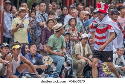 TOKYO, JAPAN - AUGUST 26TH, 2017. Spectators waiting by the roadside at the Asakusa Samba Carnival Parade in Tokyo.