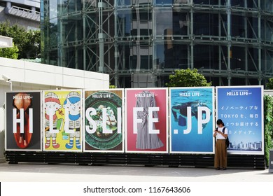 TOKYO, JAPAN - August 28, 2018: A visitor in Roppongi using a smartphone stands in front of line of billboards advertising the Hills Life website. Roppongi Hills is in the background.