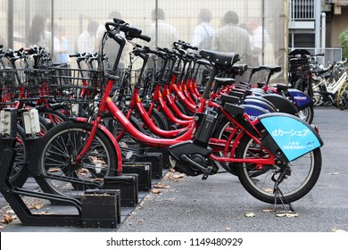 TOKYO, JAPAN - August 3, 2018: E-bikes belonging to Toyko's public bicycle sharing scheme in a parking area in front of a designated smoking zone in Tokyo's Toranomon area.