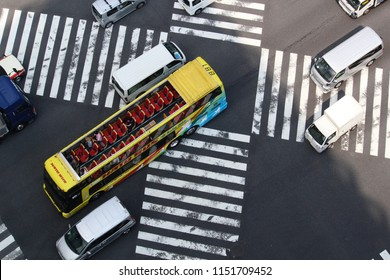 TOKYO, JAPAN - August 3, 2018: Overhead view of vehicles, including an open top Hato tour bus, crossing Ginza's Sukiyabashi scramble crossing on a extremely hot summer's day. Some motion blur.