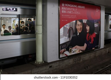 TOKYO, JAPAN - August 3, 2018: View of a billboard, a Hong Kong Airlines as featuring Jackie Chan, at Roppongi subway station with a  Hibiya line train subway train on opposite platform.