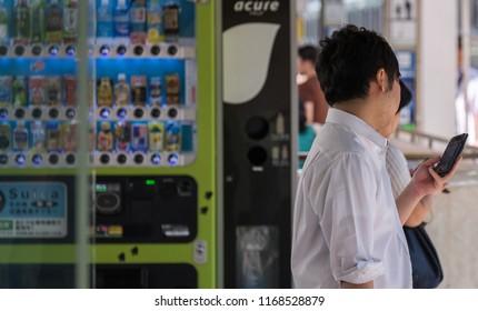 TOKYO, JAPAN - AUGUST 30TH, 2018. Man with smartphone at Tokyo Railway Station platform.