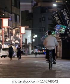 TOKYO, JAPAN - AUGUST 3RD, 2018. Man riding a bicycle Asakusa back alley at night.
