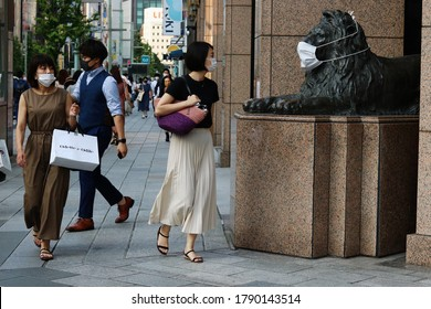 TOKYO, JAPAN - August 5, 2020: People notice a statue of a lion at an entrance to Mitsukoshi Department Store in Ginza in central Tokyo. It's wearing a mask during the coronavirus outbreak.