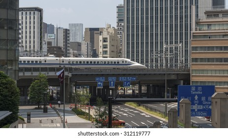 TOKYO, JAPAN - AUGUST 7:  A Tokaido shinkansen bullet train speeds across a bridge over a city street in Tokyo shown on August 7, 2015 in Tokyo, Japan