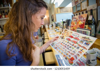 Tokyo / Japan - August 7th 2018: Woman ordering sushi at a restaurant in the Tsukiji Fish Market