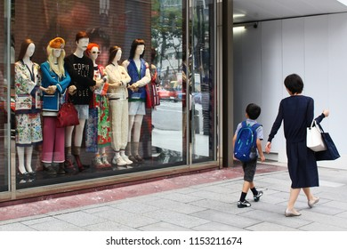 TOKYO, JAPAN - August 9, 2018: Pedestrians look at a Gucci store's striking window display as they walk along a street in Toyko's Ginza area.