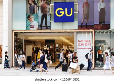 TOKYO, JAPAN - August 9, 2018: A large GU clothes store and the crowded sidewalk in front of it in Ginza in central Tokyo. GU is owned by Fast Retailing which also owns Uniqlo.