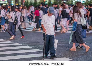 TOKYO, JAPAN - AUGUST 9TH, 2017. Old man crossing the famous Shibuya scramble