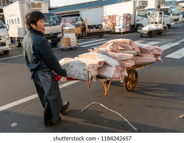 Tokyo, Japan - CIRCA 2018: Tsukiji fish market is the largest wholesale fish and seafood market in the world, handling over 2,000 tons of marine products per day. Man and cart.