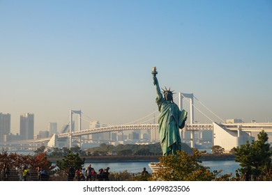 TOKYO, JAPAN – CIRCA JULY 2018: Closeup of copy of the Statue of Liberty, a popular tourist attraction, located in Odaiba Marine Park, with views of the Rainbow Bridge the the Tokyo skyline.