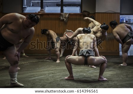 TOKYO, JAPAN - CIRCA JUNE 2014 - A group of sumo wrestlers stretch and warm up before a training session. The sumo training sessions last over 3 hours but stretching makes up the basis of training.