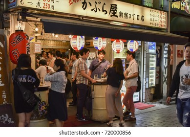 TOKYO, JAPAN - CIRCA September 2016: People stand and have a drink in izakaya