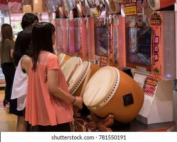 Tokyo, JAPAN - CIRCA September 2016: Young woman plays video game in Tokyo arcade
