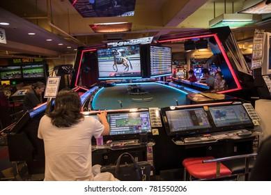Tokyo, JAPAN - CIRCA September 2016: Young man plays video game in Tokyo arcade