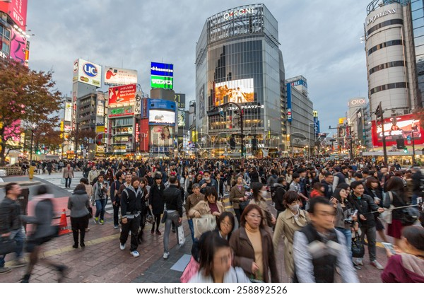 TOKYO, JAPAN - DEC 01, 2014: Shibuya is famous for its scramble crossing. It stops vehicles in all directions to allow pedestrians to inundate the entire intersection.