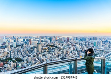 Tokyo, Japan - Dec 6, 2017 : Tourists take shot of Tokyo Tower under bright golden sun and vivid twilight sky in Roppongi Hill, Tokyo, Japan