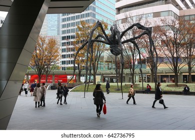 TOKYO, JAPAN - DECEMBER 1, 2016: People walk by Roppongi Hills spider monument in Tokyo, Japan. The Spider is a popular meeting place for local people.