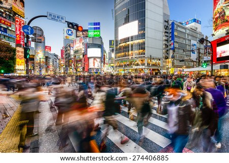TOKYO, JAPAN - DECEMBER 14, 2012: Pedestrians walk at Shibuya Crossing during the holiday season. The scramble crosswalk is one of the largest in the world.