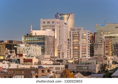 TOKYO, JAPAN - December 15 2018: Bird's view of the Japanese youth culture fashion's district of Harajuku backstreets  with Roppongi Hills and TOD'S Omotesando buildings in background at sunset.