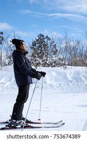 Tokyo, Japan December 2016 : Asian girl having fun skiiing on white snow mountain with beautiful blue sky