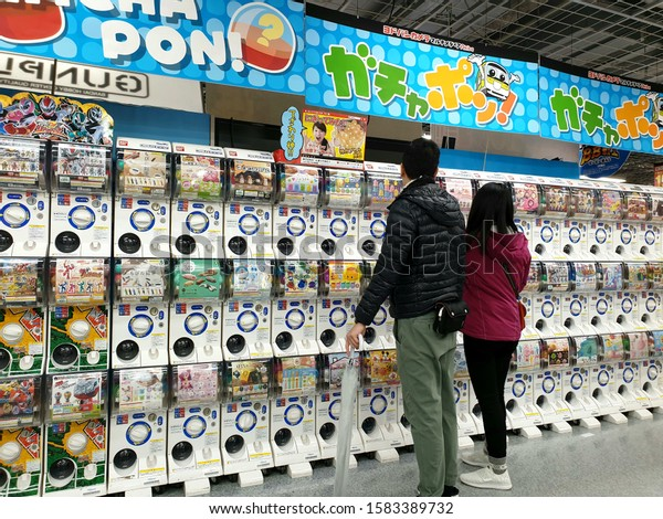 Tokyo, Japan - December, 2019: Visitors are standing in front of a huge variety of capsule toy or gachapon machines in the Yodobashi electronics store in Akihabara district.