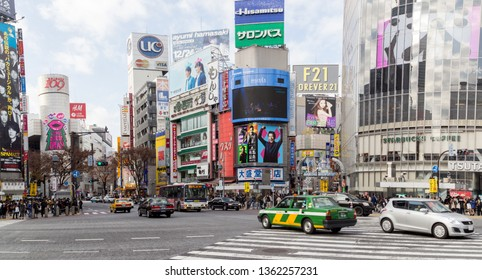 Tokyo, Japan - December 21, 2014: Cars and people at the famous Shibuya crossing in Tokyo.