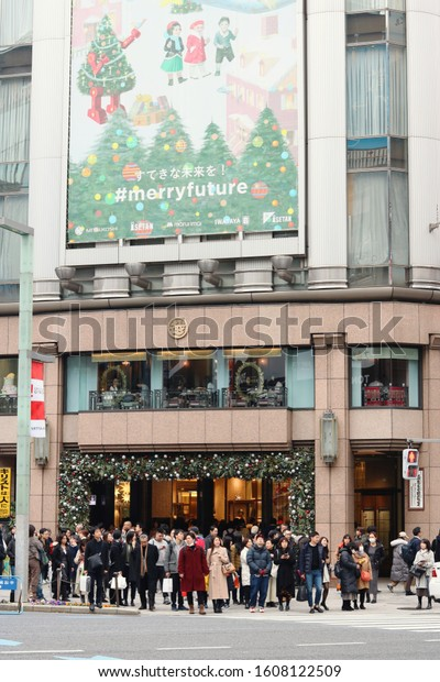TOKYO, JAPAN - December 22, 2019: Pedestrians wait to cross the street in front of the Ginza's Mitsukoshi Department store. It's Christmas so the store has a festive billboard.
