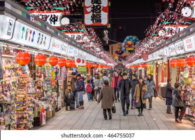 TOKYO, JAPAN - DECEMBER 23, 2015: Visitors to Senosoji Temple walk through Nakamise Shopping Street. The shop lined pedestrian street stretches from the first gate to the main temple grounds.