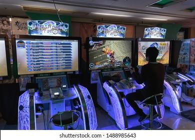 TOKYO - JAPAN - DECEMBER 26, 2015: A man plays Gunslinger Stratos, a four-versus-four third-person shooter, inside Taito arcade store.