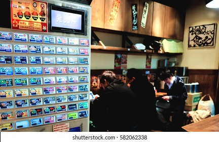 TOKYO, JAPAN - DECEMBER 27, 2015 : Vending machines for order the meal in Japanese restaurant and Customers waiting for food