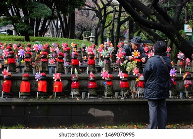 TOKYO, JAPAN DECEMBER 29 2018: Elderly Japanese Couple Tending to Little Children Funeral Death Memorial Statues Representing & Commemorating Stillborn, Miscarried & Dead Infants at Zojoji Temple