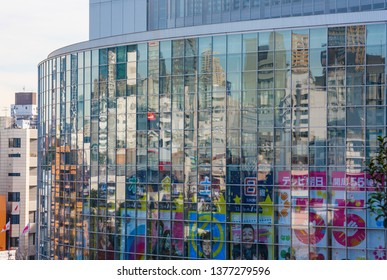 TOKYO, JAPAN - DECEMBER 30, 2013: Buildings of the Roppongi district reflecting in the glass facade of TV Asahi headquarters. TV Asahi is a japanese television network.