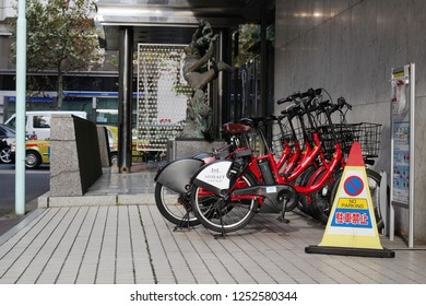 TOKYO, JAPAN - December 7, 2018: A row of electric bikes belonging to Toyko's public bicycle sharing scheme parked outside an office building in Kayabacho in central Tokyo.