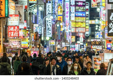 TOKYO, JAPAN - FEB 2019 : Crowd Undefined people walking around night market street at Kabukicho of shinjuku Station on Febuary 19, 2019 in Tokyo, Japanese culture and shopping neon street concept