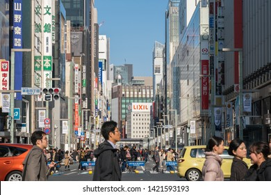 TOKYO, JAPAN - FEB 2019 : Undefined Japanese and Foreign tourists are Walking across the crosswalk around Ginza Wako and Ginza Mitsukoshi upmarket on Febuary 17, 2019, Tokyo, Japan.
