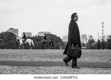 Tokyo, Japan - Feb 2nd 2009: Imperial Japan meets Modern Japan - A salaryman walks past the imperial cavalry.